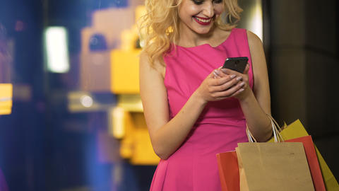 Female shopaholic checking prices of her purchases at online stores, mobile app Footage