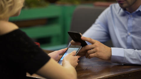 Business family concentrated on smartphones on date at restaurant, indifferent Footage