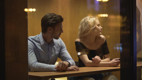 Handsome man sitting in restaurant and flirting with blond woman, relationship Live Action