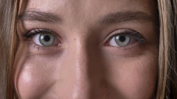 Eyes of young charming girl is watching at camera, smiling, grey background Footage