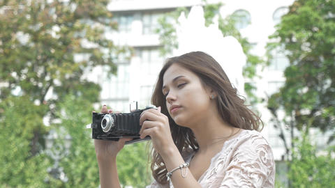 Beautiful young girl with long hair, taking pictures of sights on a vintage GIF