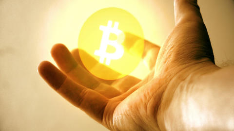 the virtual currency of a bitcoin in the hand of a business man Footage