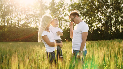 Young parents go to the field with spikelets of wheat in white T-shirts and ビデオ