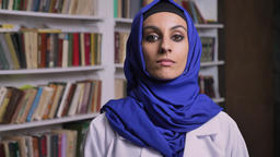 Young beautiful muslim woman in hijab standing in library and looking at camera ビデオ