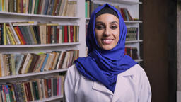 Young happy muslim woman in hijab standing in library and looking at camera and Footage