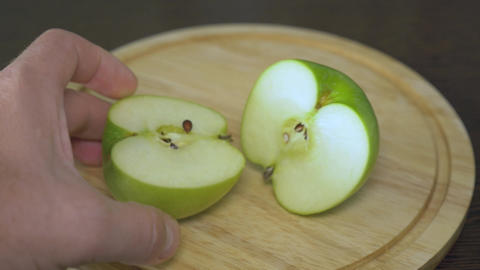Men's hands cut the green apple into two equal parts. These are vitamins and a Footage