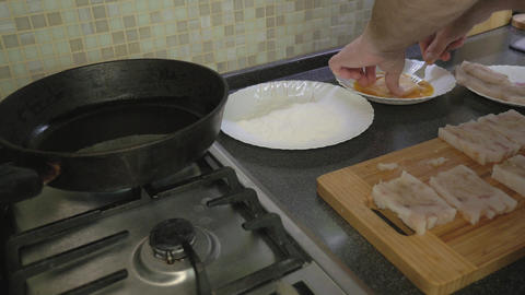 A man is cooking fish fillets at home in the kitchen GIF