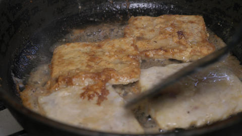 Fish fillets are turned over in a frying pan. Lots of oil, fat and cholesterol ビデオ