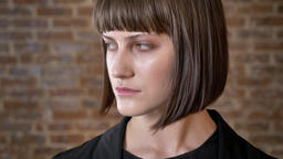 SErious young woman turning head and looking at camera, isolated on brick Footage