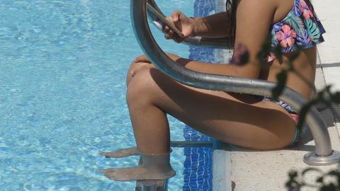 Girl Uses Smartphone On The Edge Of Swimming Pool GIF