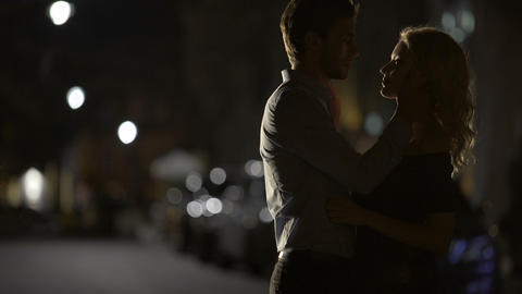 Silhouettes of loving couple embracing each other in the street, relationship Footage