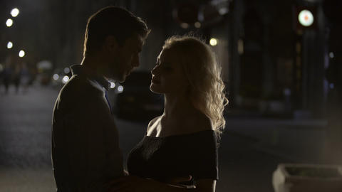 Blond female teasing and cuddling boyfriend in the night street, silhouettes Live Action