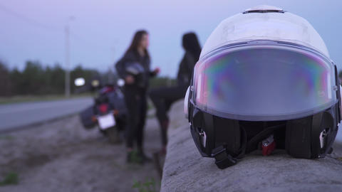 Motorcycle helmet at foreground, girls bikers relaxing after trip at background Live Action