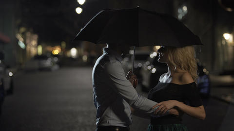 Beautiful couple of lovers embracing under umbrella, night date, love story Live Action