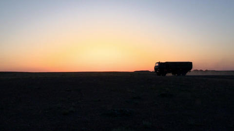 A military machine rides through the steppe at sunset ビデオ