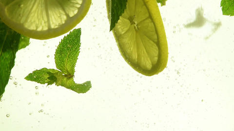 Close up ice cubes, mint leaves, lemon in mojito Footage