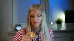 Happy woman holding bitcoin showing thumbs up. Cheerful young blond woman in Footage