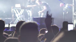 Footage of crowd raising hands and jumping at rock concert Footage