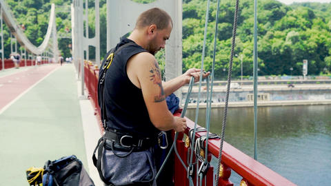 Guy lowers the rope for jumping from the bridge Live Action