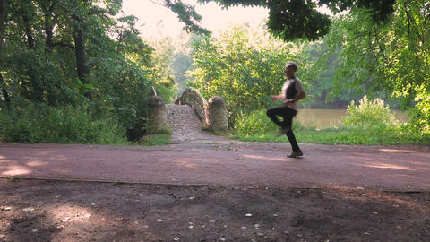 A man runs in the park on a summer day, on special tracks. He performs exercises GIF