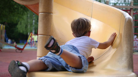 Funny toddler boy slides and falls on a slide Live Action