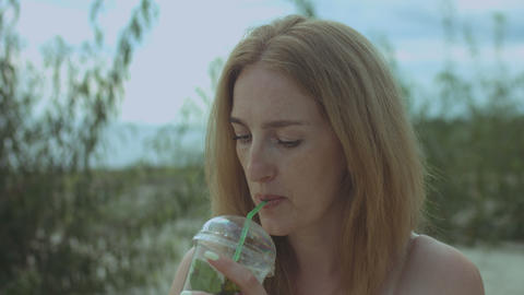 Charming redhead woman drinking cold drink on beach Footage