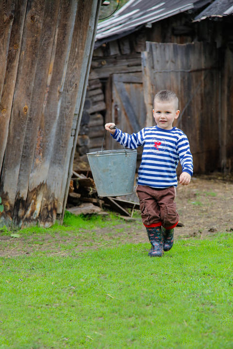 Boy in the countryside carrying a bucket フォト