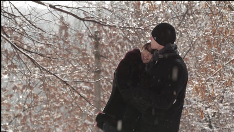 a pair of young people hugging in the winter under the snow Live Action