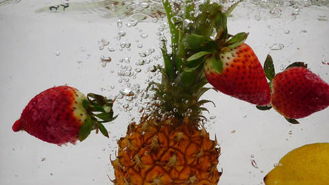 Pineapple, lemon and strawberry falling in water with bubbles. Video on isolated Footage