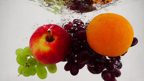 Apple, orange and grapes falling into water with bubbles in slow motion. Fruit Footage