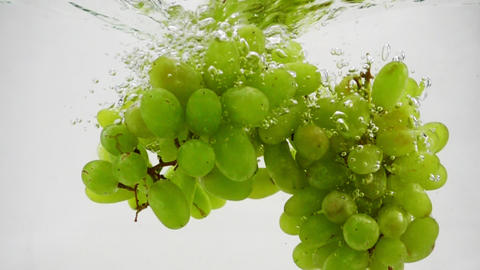 Bunch of green grapes falling into water with bubbles in slow motion. Berries on Live Action
