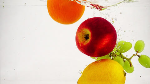 The apple,lemon, orange and grapes falling in water with bubbles in slow motion Live Action