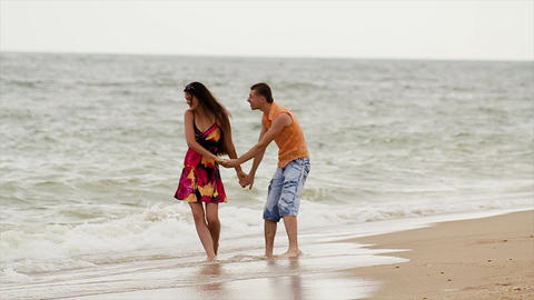 young couple in love embraces in the surf Live Action