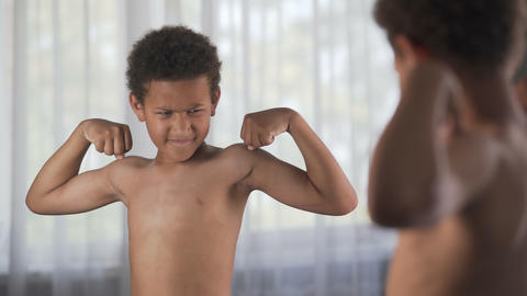 Confident kid looking at his muscles in mirror imagining that he is super hero Footage