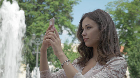 Young beautiful girl with long hair takes a picture of herself on the phone. In GIF