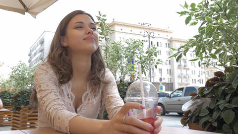 Young beautiful brunette drinks a summer cocktail while sitting at a table in a Footage