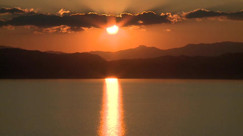 Sunset behind hills and lake Footage