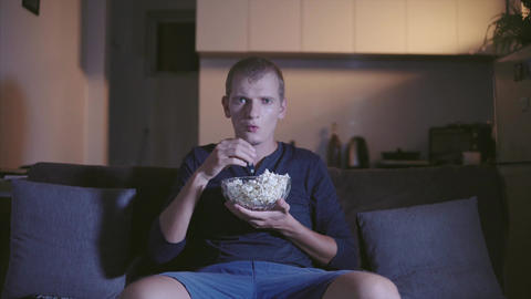 Adult Man interestedly watching tv and film seating on comfortable sofa and Footage