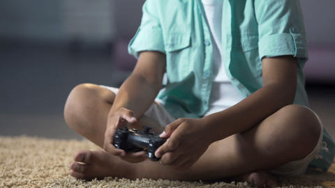 Child aggressively pressing joystick buttons controlling character on console Footage
