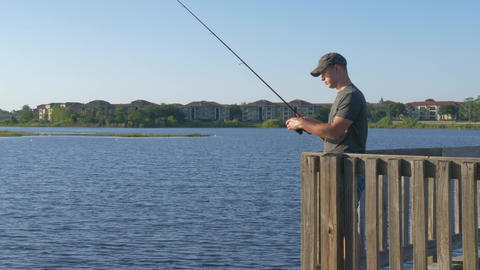 Fisherman cast fishing rod in lake or river water Footage
