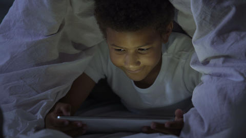Little kid looking at tablet secretly at night, covered with head in blanket Live Action
