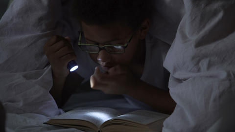 Child reading books at night under blanket, lighting… Stock Video Footage