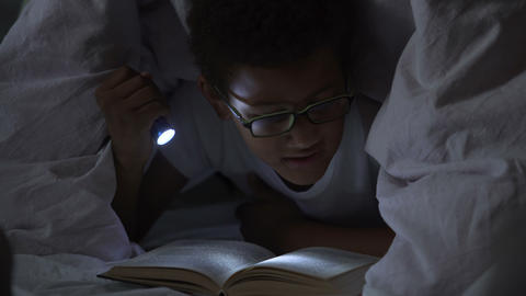 Child reading books at night under blanket, lighting himself with flashlight Footage