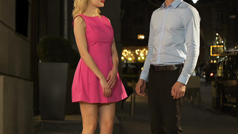 Blond girl giving hand to guy, couple hugging in street, love relationship, date Footage