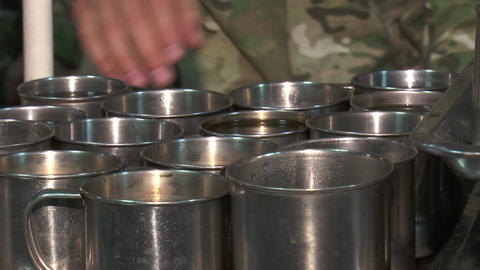 Military soldiers take metal mugs with compote Live Action