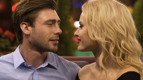 Male looking passionately at woman, couple nuzzling in restaurant, affectionate Live Action