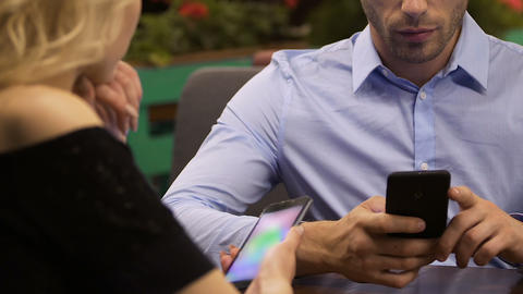 Man using mobile phone at table while woman talking to him, irritation, crisis Live Action