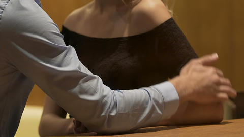 Woman and man at bar table touching each other gently face to face, pick-up Live Action