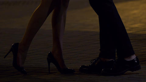 Man and woman kissing in street at night, romantic relationship, legs in shot Live Action