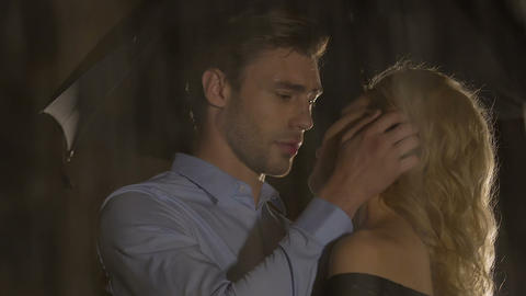 Man caressing beautiful young woman under umbrella on rainy evening, attraction Footage